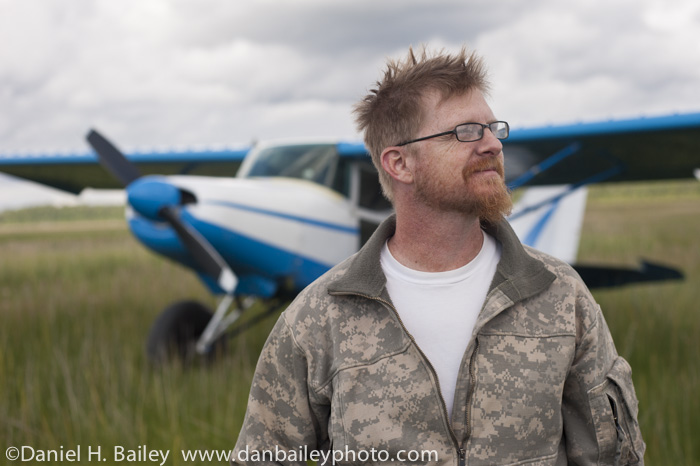 Portrait of Chet Harris and his Maule M5 airplane in a tall grass field, Alaska