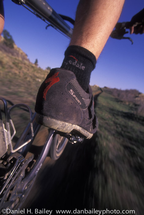 Closeup of a mountain biker's feet pedaling on the trail