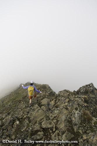 Hiker at the edge of the fog. Chugach Mountains, Alaska