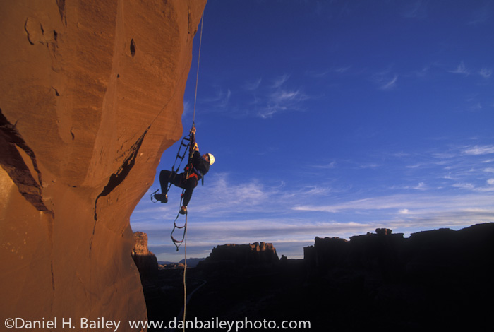 Rock climber jugging fixed lines in the Canyonlands, Arches National Park, Utah