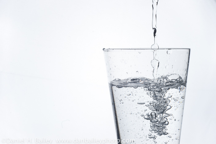 High speed flash shot of water being poured into a glass.