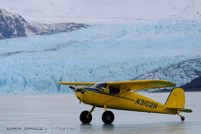 Cessna 120 parked on frozen Lake George in front of Colony Glacier, Alaska